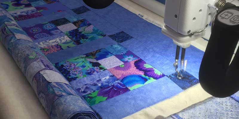 A lovely colourful quilt being quilted with popular baptist fan design