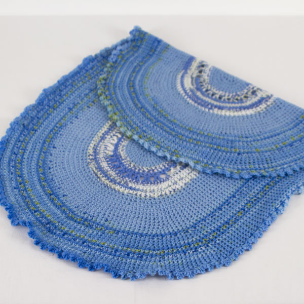 Oval-Blue-Variegated-crochet-blanket-with-frilly-edge-folded-back-CB106