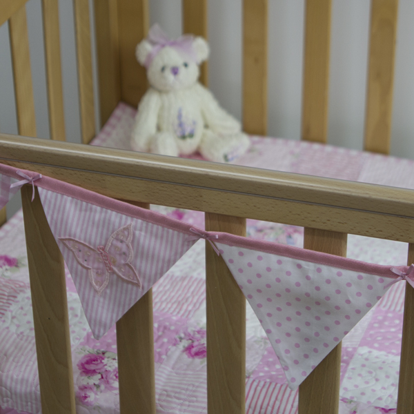 Applique embroidered butterfly bunting in pink on cot