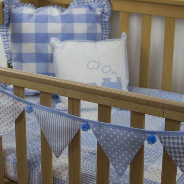 Baby blue bunting blue pom-poms on cot with My Little Train quilt