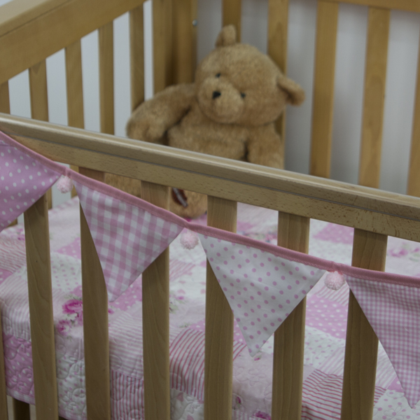 Baby pink bunting with pink pom-poms on cot