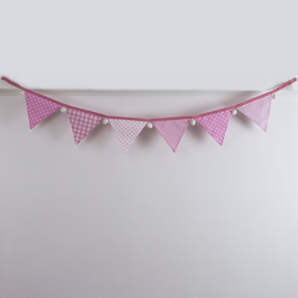 Baby pink bunting with white pom-poms front-on
