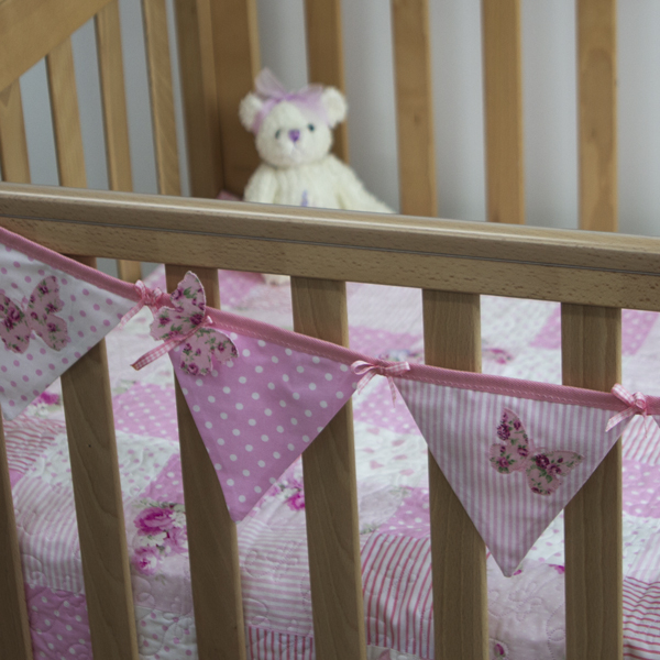 Flutterby Butterfly bunting in pink on cot with Flutterby Butterfly quilt