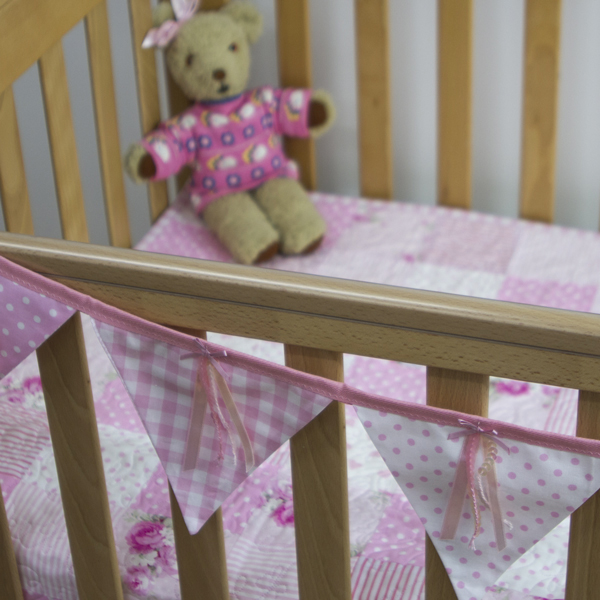 Ribbons and sequins bunting in pink on cot